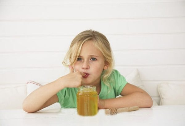 Девочка ест мёд