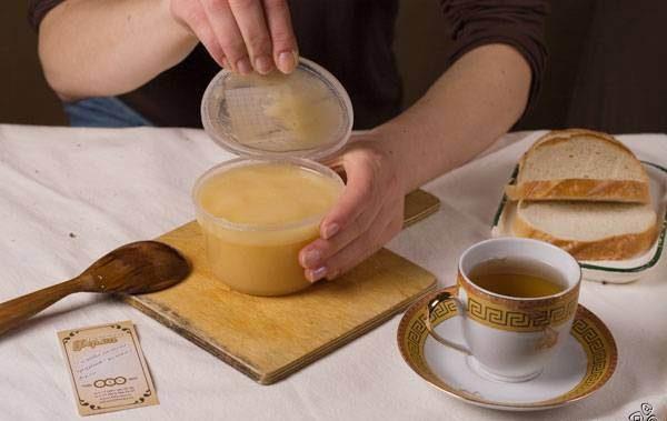 Рапсовый мёд в пластиковой банке на столе