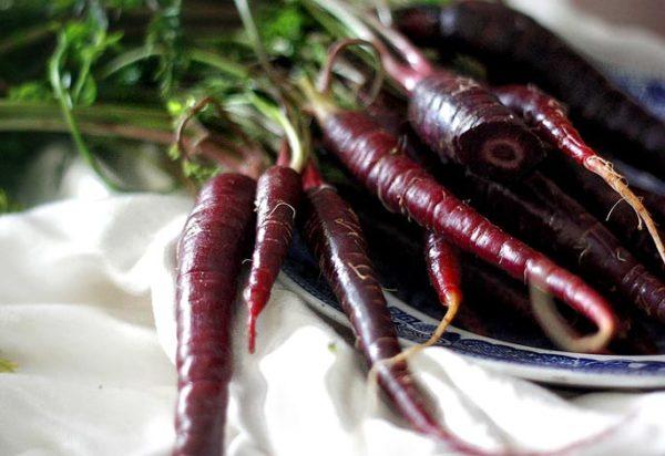 Плоды черной моркови на тарелке